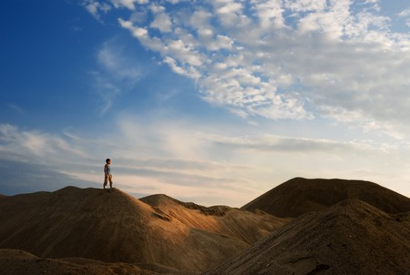 young man go up in sand desert in sundown silhouette Stock Photo