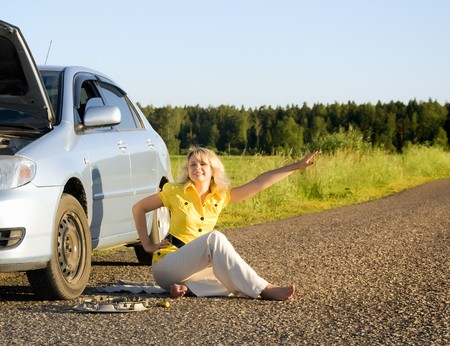 Girl standing by the side of the road with the hood of her car open signaling problems with the car photo