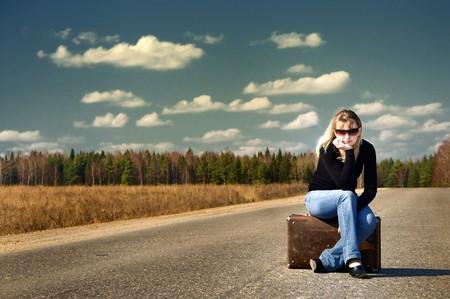 hübsches Mädchen auf der Straße mit Ihrem Gepäck warten