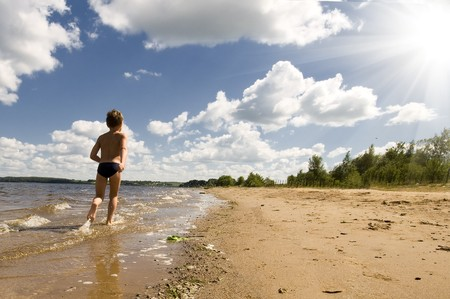 young boy running at the beautiful beach of river photo
