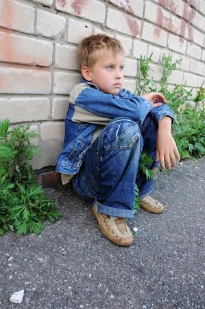 ni�os tristes: un joven se sienta contra graffiti por s� sola  Foto de archivo