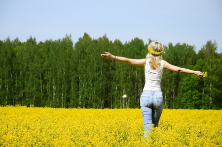 happy young woman is standing on a flower field