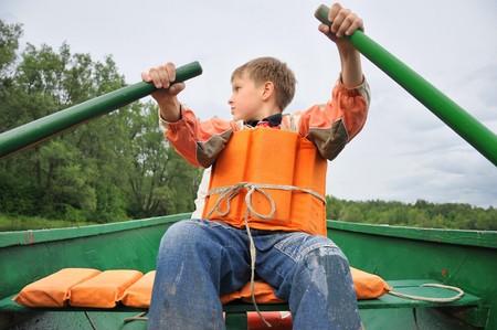 Junger Mann Rudern ein Boot auf dem Fluss.