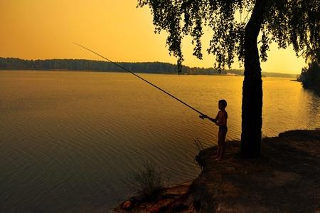 fishing on shoreline at dusk during a sunset. Stock Photo