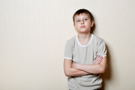 upset small boy stands against a wall Stock Photo