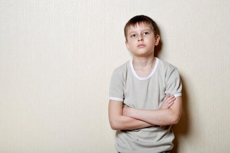 verärgert kleiner Junge steht gegen eine Wand Standard-Bild