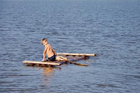 jangada: Joven en balsa en el r�o de agua Foto de archivo