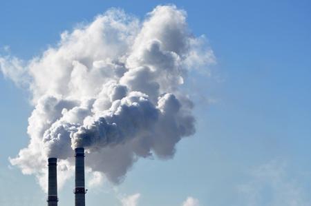 residuos toxicos: el humo de la chimenea industrial en el cielo azul Foto de archivo