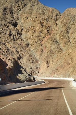 Leere Straße überqueren einen trockenen Berg in der Wüste