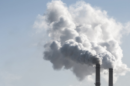 carbon emission: industrial smoke from chimney on blue sky