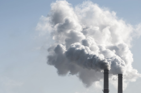 exhaust gases: industrial smoke from chimney on blue sky