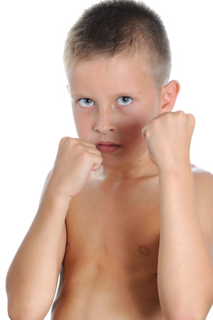 Serious and determined young boy wearing like boxing gloves and looking at the camera. Isolated on white photo