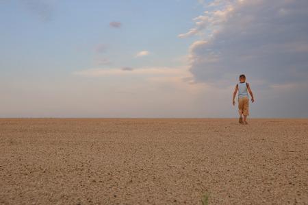 young man go up in sand desert in sundown photo