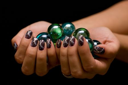 Exotic Manicure for young woman cosmetic with balls decoration. Isolated on black background.
