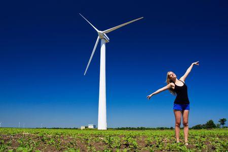 Model posing in front of wind power generator photo