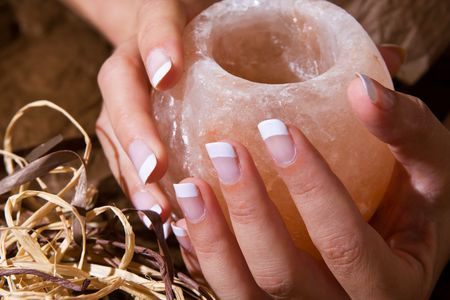 Woman's hand with French manicure holding exotic salt-crystal candlestick