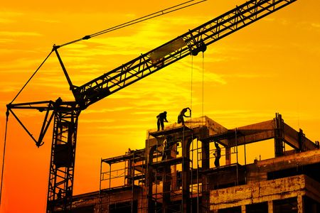 job site: Worker on roof and crane on construction site silhouetted against orange sunset