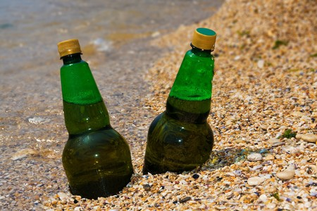 Cold beer on beach sand photo