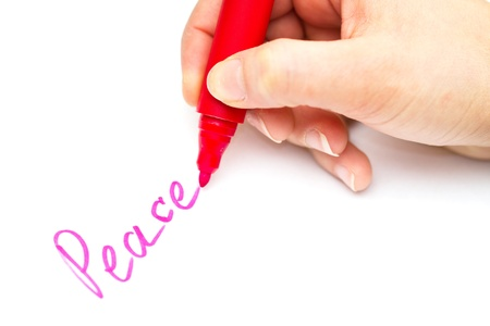 Kid writing peace on white paper with red color photo