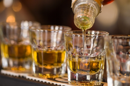 Barman makes whisky shot drinks in row  Alcoholic shots in nightclub Stock Photo