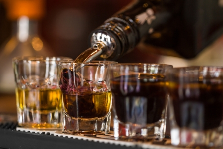 Barman make alcoholic shots with whisky and liqquor in nightclub