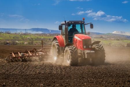 Gloednieuwe rode tractor op het veld werken Stockfoto