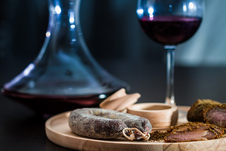 cold cuts: Meat fillet and sausage eith red wine on cutting wooden plateau Stock Photo