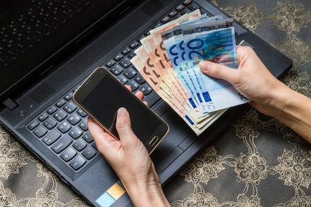 Woman is using smart phone for on line payment. Mobile shopping concept with euro money.
