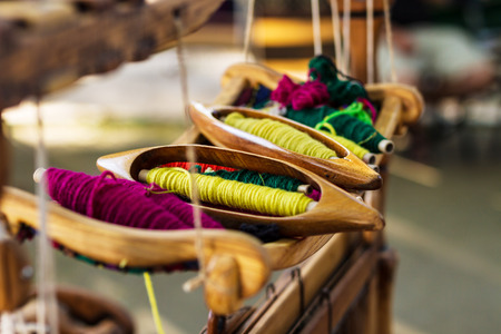 weaving: A closeup image of an old weaving Loom and thread of yarn.