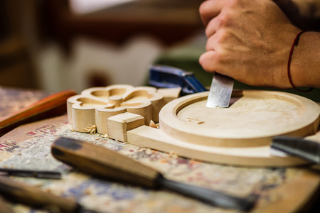 engraver: Carpenter hand carving wood with care. Hand with tool blured in motion.