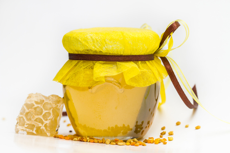 apiarist: Herbal honey in jar with small honeycomb and herbs isolated on white background Stock Photo