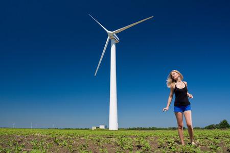 Female at wind power generator turbine - alternative and green energy source