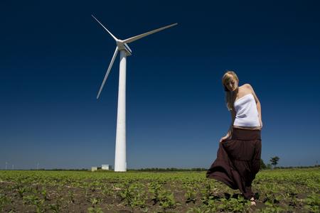 turbine: Female at wind power generator turbine - alternative and green energy source