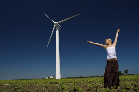 green power: Female at wind power generator turbine - alternative and green energy source