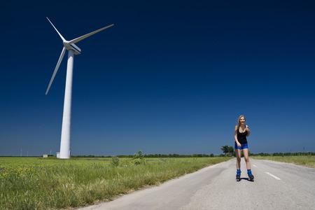 turbina: Mujer en el viento generador de potencia de la turbina - fuente de energía alternativa y verde