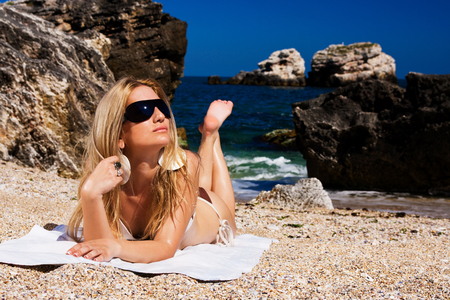 summer beach: Smiling woman in suimsuit standing on beach, sunny summer day