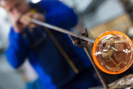 material de vidrio: soplador de vidrio que forma hermosa pieza de vidrio. Un artesano de vidrio se está quemando y soplando una obra de arte.