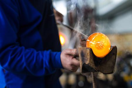 Glas-Gebläse bilden schöne Stück Glas. Ein Glas Crafter brennt und bläst ein Kunstwerk. Standard-Bild