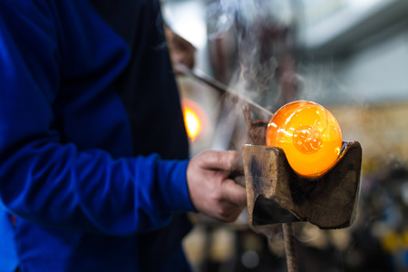 commercially: Glass blower forming beautiful piece of glass. A glass crafter is burning and blowing an art piece.