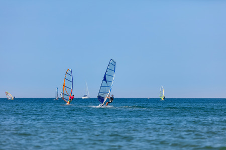 A man on windsurf conquering the waves. Summer on the beach.