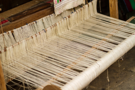 rug weaving: A closeup image of an old weaving Loom and thread of yarn.