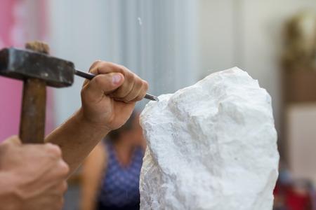 canicas: Joven estudiante en el trabajo aprendizaje profesión artesano en la clase de arte, trabajando con martillo para tallar estatua de piedra de piedra blanca