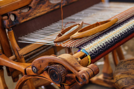 hand woven: A closeup image of an old weaving Loom and thread of yarn.