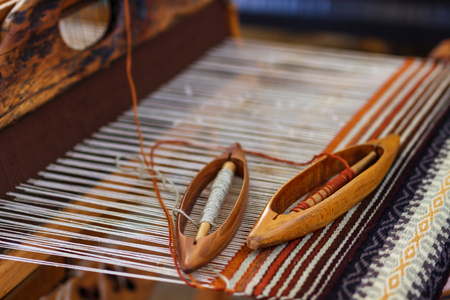 A closeup image of an old weaving Loom and thread of yarn.