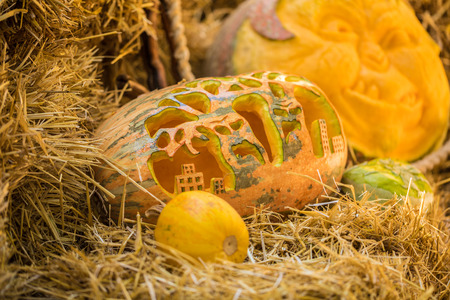 Helloween pumpkin on hay at old wooden farm house Stock Photo