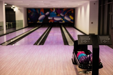 sphere standing: Bowling balls and wooden lane in bowling hall Stock Photo