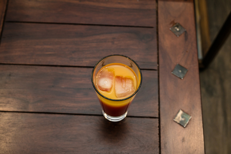 Fresh orange fruit juice with ice on a wooden table