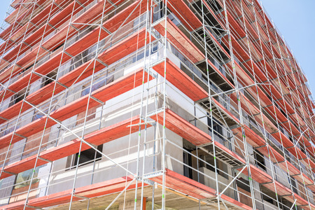 Building construction site with red scaffolding. Building facade. Stock Photo
