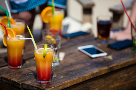 Alcohol orange daiquiri and cuba libre cocktail on beach bar rustic wooden table. Stock Photo