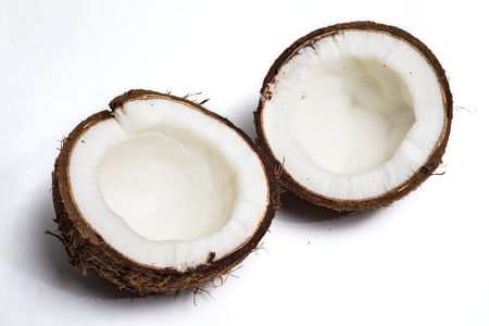 Broken coconut isolated on a white background with coconut milk Stock Photo